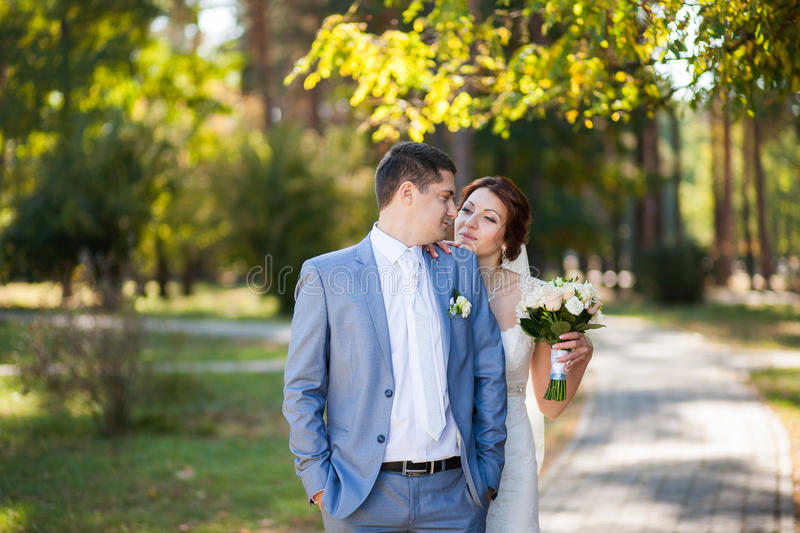 Happy bride, groom standing in green park, kissing, smiling, laughing. lovers in wedding day. happy young couple in love. stock photo