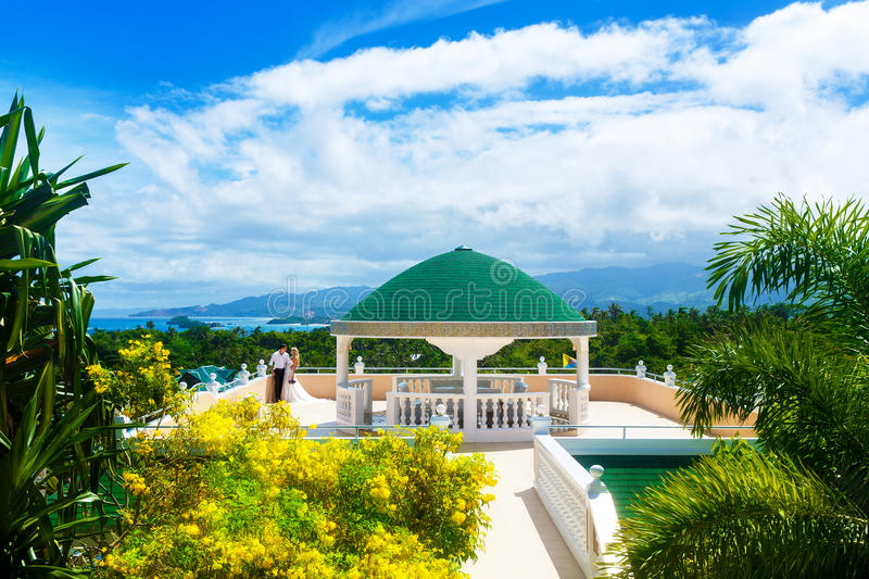 Happy bride and groom standing next to the stone gazebo amid beautiful tropical landscape. Sea, sky, flowering plants and palm tr stock images