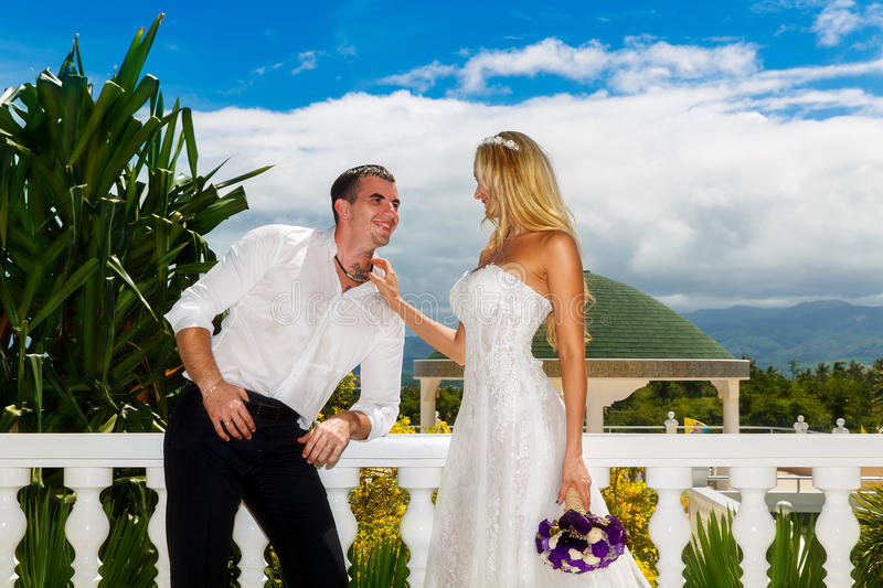 Happy bride and groom standing next to the stone gazebo amid beautiful tropical landscape. Sea, sky, flowering plants and palm tr. Ees in the background. Wedding royalty free stock image