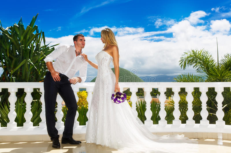 Happy bride and groom standing next to the stone gazebo amid beautiful tropical landscape. Sea, sky, flowering plants and palm tr. Ees in the background. Wedding stock photo