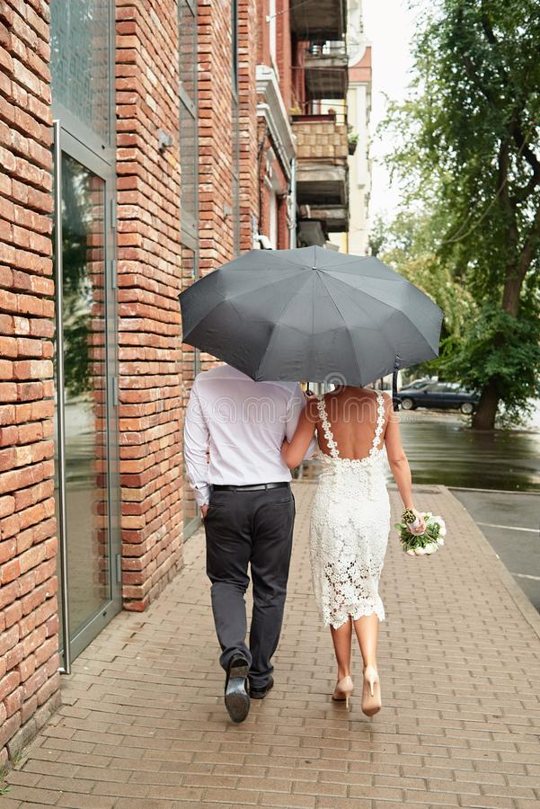 Happy bride and groom with umbrella walking on the street in city outdoors, copy space. Wedding couple in love, newlyweds. Wedding stock image