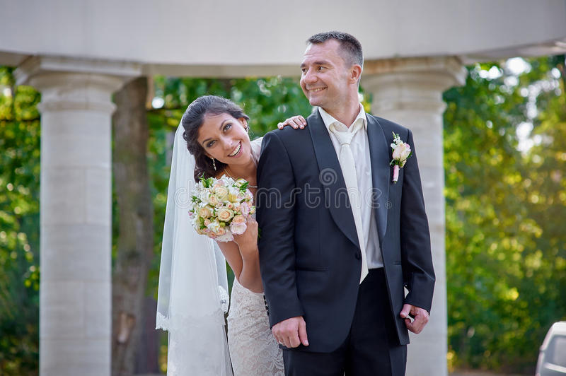 Happy bride and groom walking among the columns royalty free stock photography