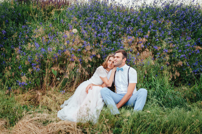 Happy Bride and groom walking on the green grass stock photo