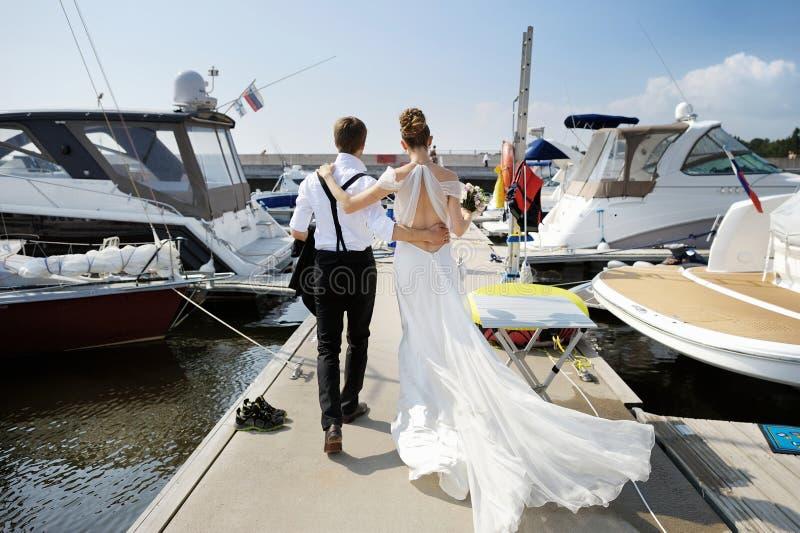 Happy bride and groom walking on pier stock photos