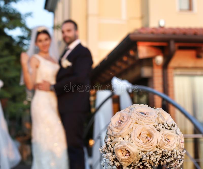 Happy bride and groom in wedding day. Wedding couple in love, newlyweds. Wedding concept. wedding bouquet in the foreground royalty free stock image