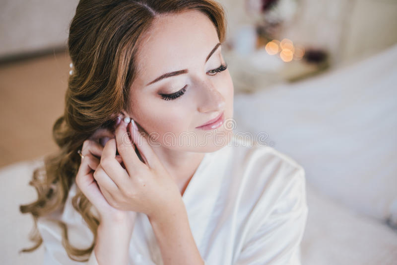Happy bride having her wedding preparations. Wedding hairstyle. Happy bride having her wedding preparations in a cozy bedroom stock photography
