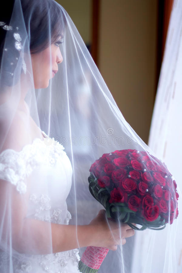 Happy Bride. Holding her bouquet looking through the window