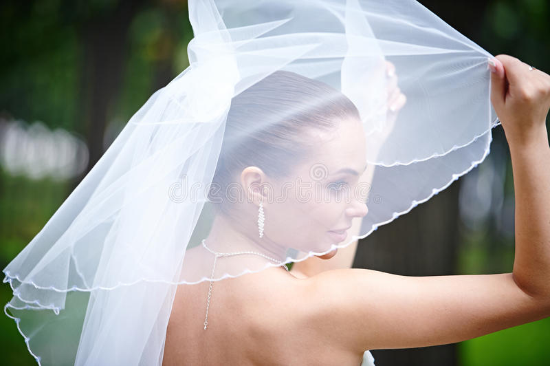 Happy bride keeps veil. Happy bride keeps her wedding veil royalty free stock photography