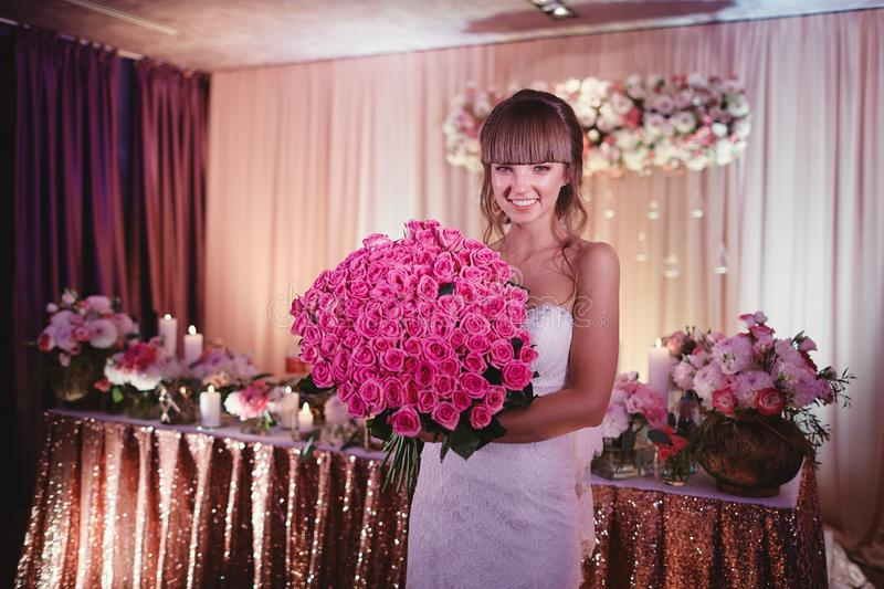 Happy bride with a large bouquet of roses. beautiful young smiling bride holds large wedding bouquet with pink roses royalty free stock image