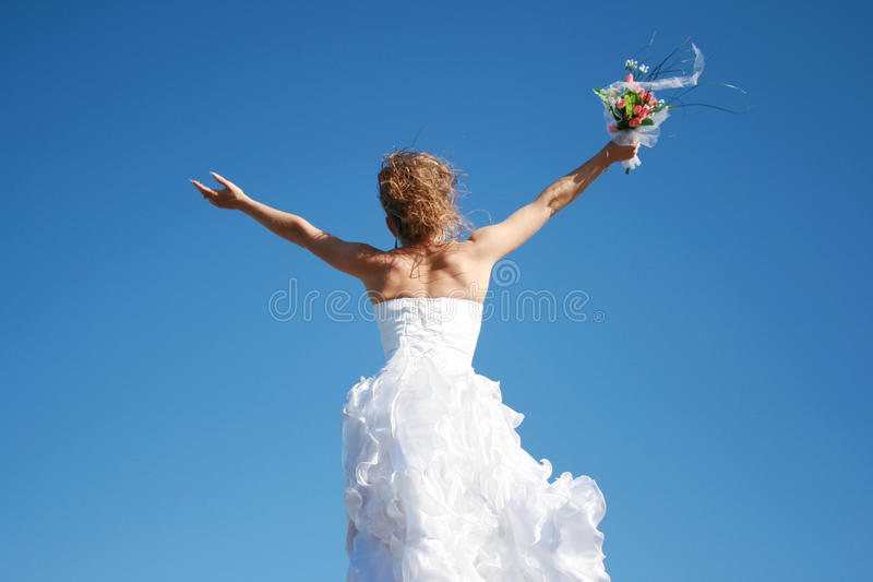 Happy bride meeting new life. Against the blue sky stock image