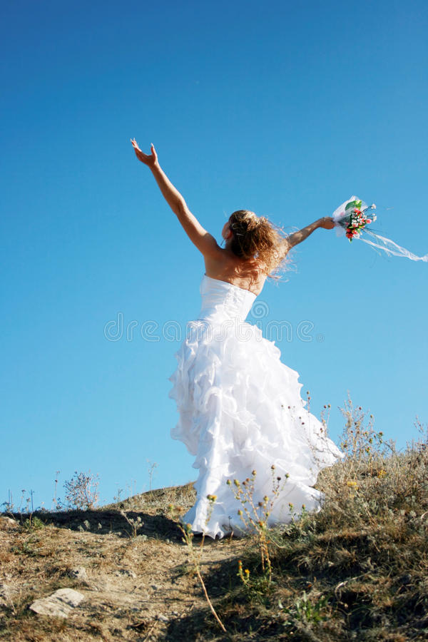 Happy bride meeting new life. Against blue sky royalty free stock photography