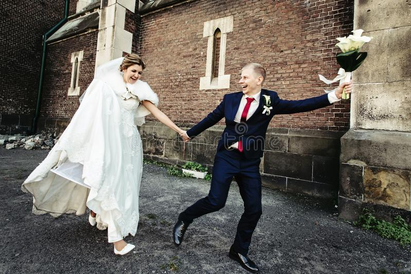 Happy bride and stylish groom running with funny emotions on the. Background old sunny city royalty free stock image