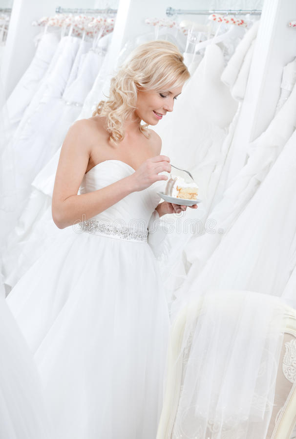 Happy bride tastes the pie royalty free stock photo