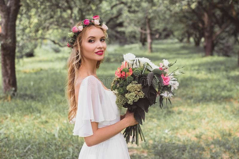 happy bride in wedding dress and floral wreath holding bouquet of flowers and smiling at camera stock photo