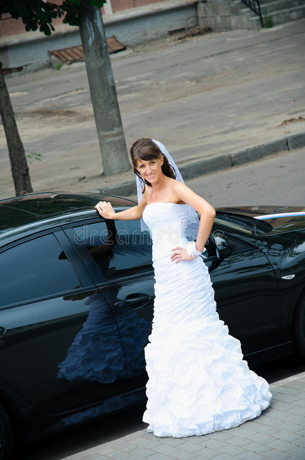 Happy bride in white dress standing near wedding car royalty free stock photo