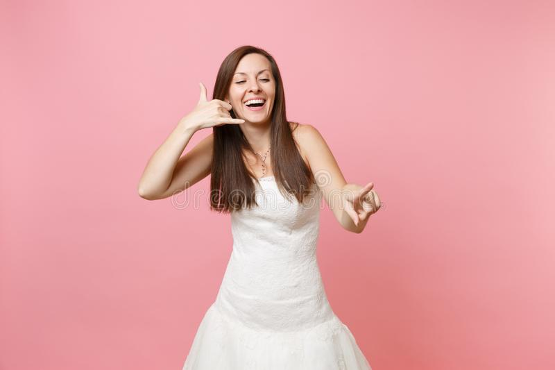 Happy bride woman in wedding dress doing phone gesture like says: call me back with hand and fingers like talking on stock images