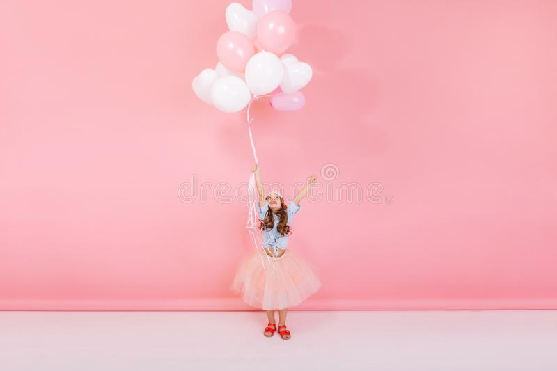 Happy brightful image of excited joyful little girl in tulle skirt holding ribbon with flying balloons  on pink. Background. Looking above, expressing happiness stock image
