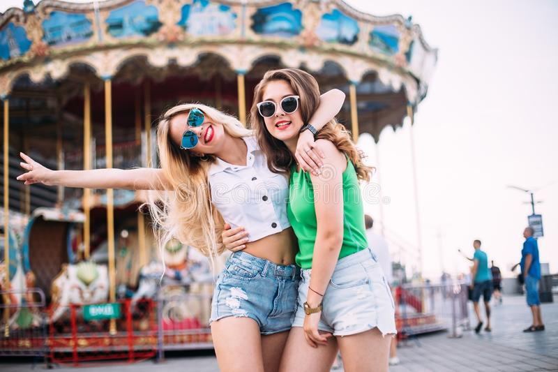 Happy brightful positive moments of two stylish girls hugging on street in city. Closeup portrait funny joyful attarctive young wo. Men having fun, smiling royalty free stock image