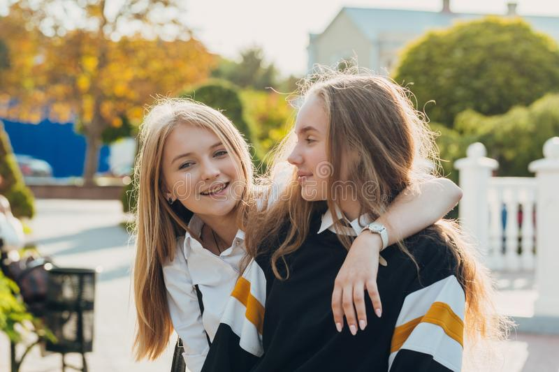 Happy brightful positive moments of two stylish girls hugging on street in city. Closeup portrait funny joyful attarctive young stock photography