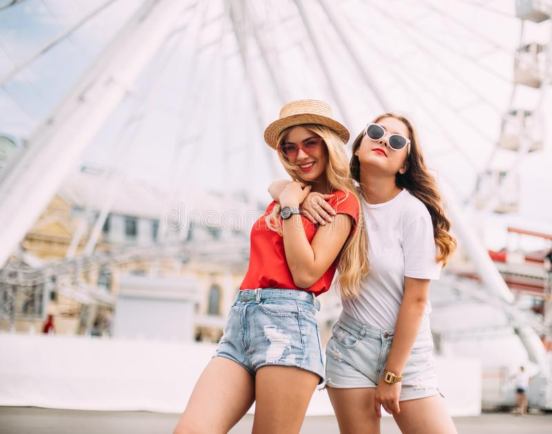 Happy brightful positive moments of two stylish girls hugging on street in city. Closeup portrait funny joyful attarctive young wo. Men having fun, smiling stock photography