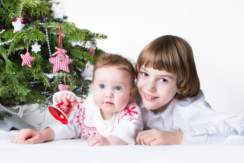 Happy brother and baby sister playing together under a Christmas royalty free stock images