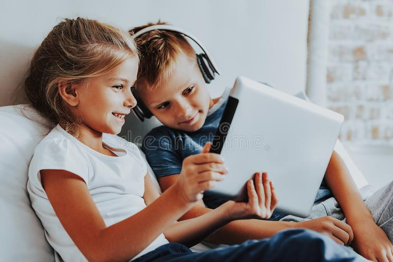 Happy brother and sister spending time with gadgets royalty free stock image