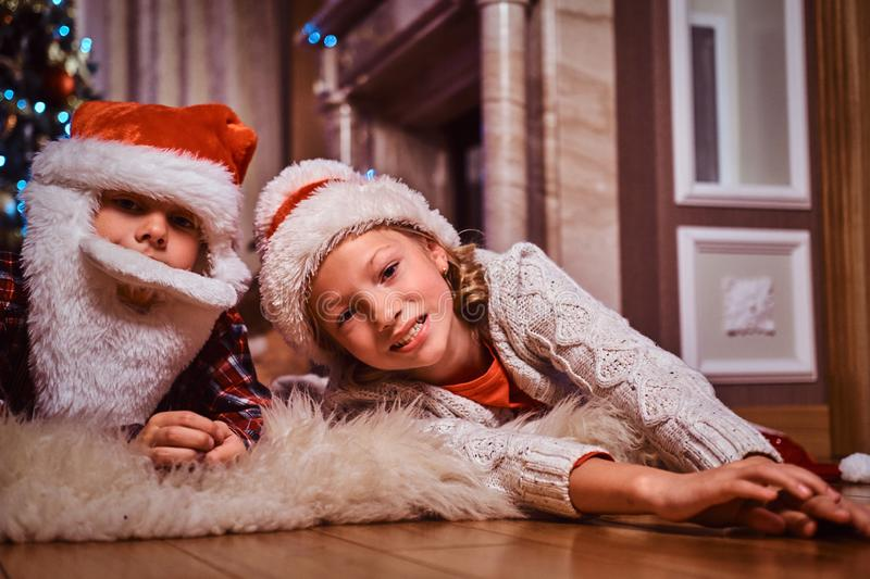 Happy brother and sister wearing santa hat lying on a fur carpet near a Christmas tree at home. royalty free stock images