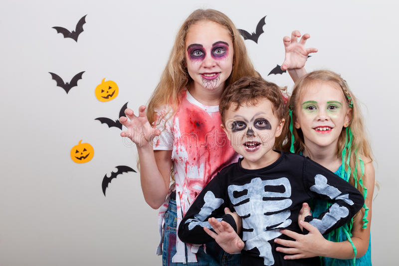 Happy brother and two sisters on Halloween party. People having fun indoor. Children wearing costumes zombies, skeletons and witches. Concept of children ready royalty free stock photos