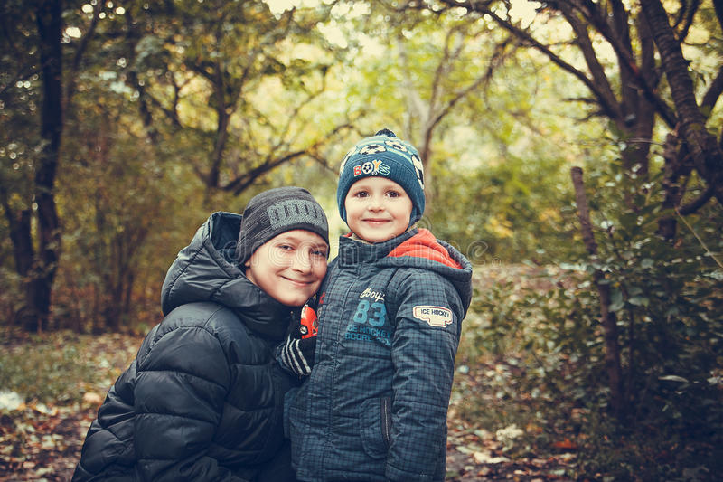 Happy brothers in autumn forest photo. Picture of two happy brothers in the autumn forest stock photo