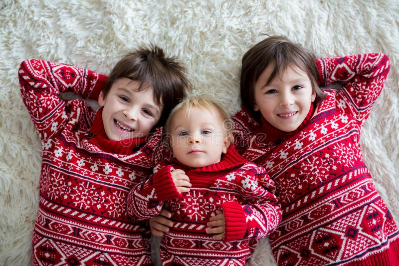 Happy brothers, baby and preschool children, hugging at home on white blanket, smiling stock images