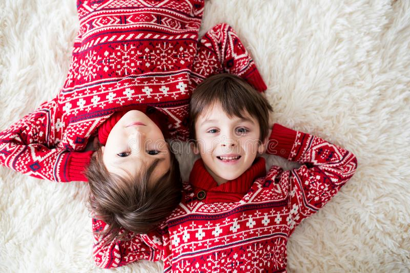 Happy brothers, baby and preschool children, hugging at home on white blanket, smiling stock photography