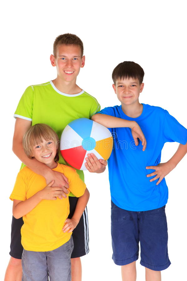 Happy brothers holding ball. Three happy smiling brothers colorfully dressed in t-shirts and shorts holding a large multicolored ball royalty free stock photo