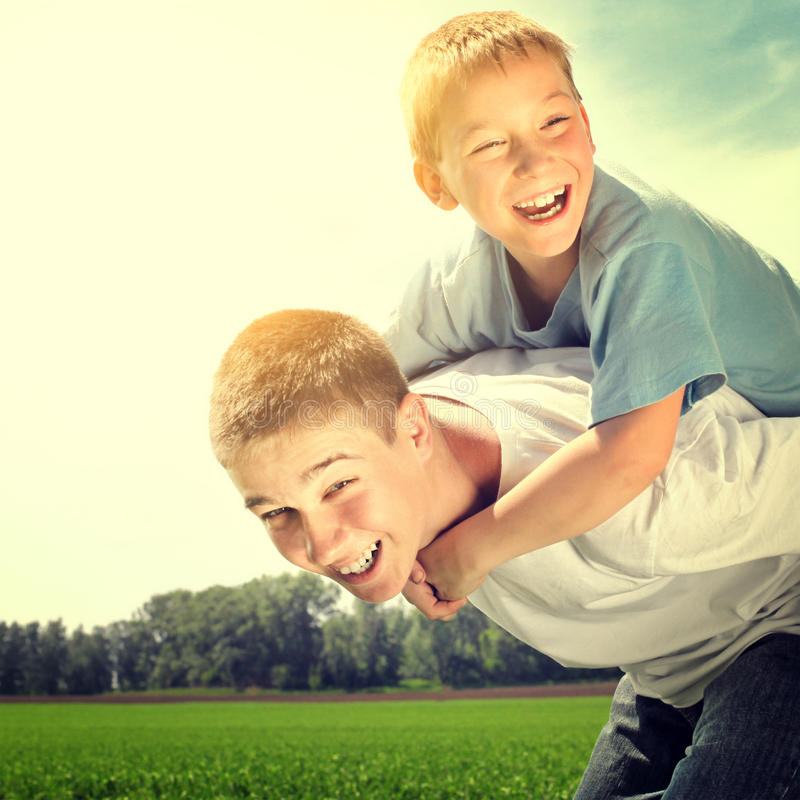 Happy Brothers outdoor. Toned photo of Happy Brothers playing at the Summer Field royalty free stock photography