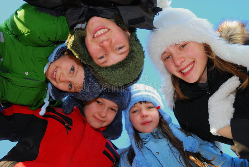 Happy Brothers And Sisters. Family of five brothers and sisters standing in a circle outdoors in winter, leaning forward toward photographer in the middle. Taken stock photos