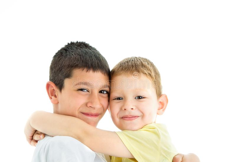 Happy brothers on white. Two happy joyful and loving  brothers isolated on white background.Smilling at camera.Four years and nine years old royalty free stock image