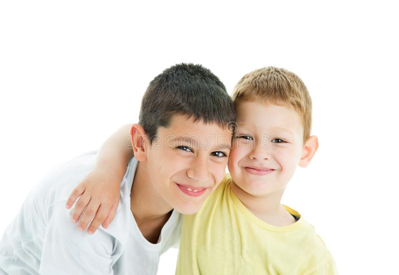 Happy brothers on white. Two happy joyful and loving  brothers isolated on white background.Smilling at camera.Four years and nine years old royalty free stock photos
