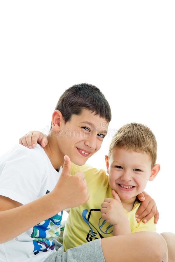 Happy brothers on white. Two happy joyful and loving  brothers isolated on white background.Smilling at camera.Thumbs up.Four years and nine years old royalty free stock photography
