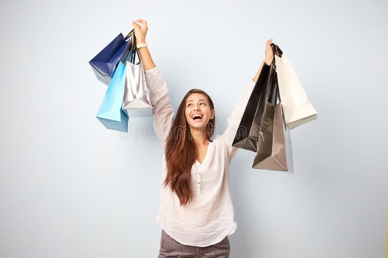 Happy brown-haired girl dressed in white blouse and gray trousers stands with lots of bags after shopping on the white stock photography