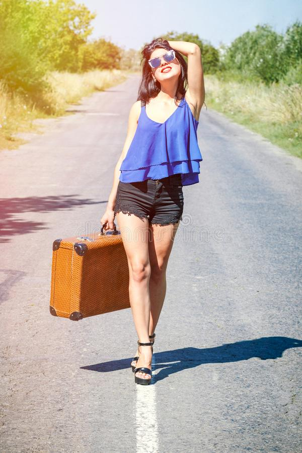Happy Brunette beautiful girl traveler with suitcase on road, hitchhiking. Concept of travel, adventure, vacation, freedom. Waitin. G for car or bus stock photos