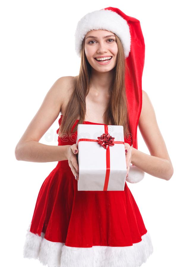 Happy brunette girl in Christmas dress and santa hat holding a white gift box. Isolated on white background. royalty free stock image