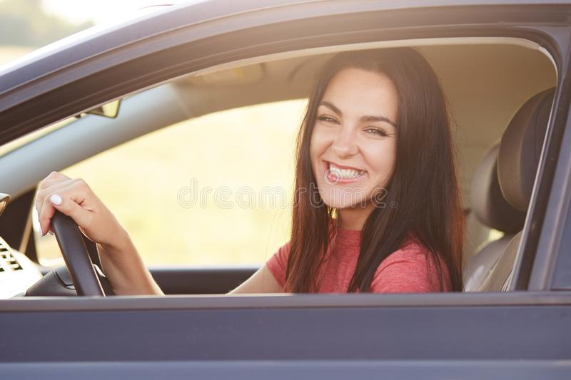 Happy brunette female driver with broad smile, drives automobile, happy to recieve it as present from husband, enjoys good roads d royalty free stock image