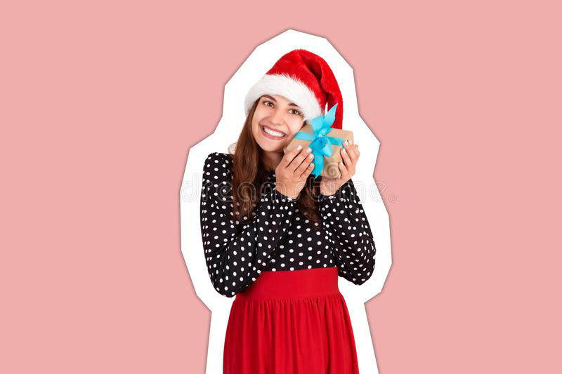 Happy brunette girl in christmas hat hugs the gift box. isolated on white background. Magazine collage style with trendy color stock image
