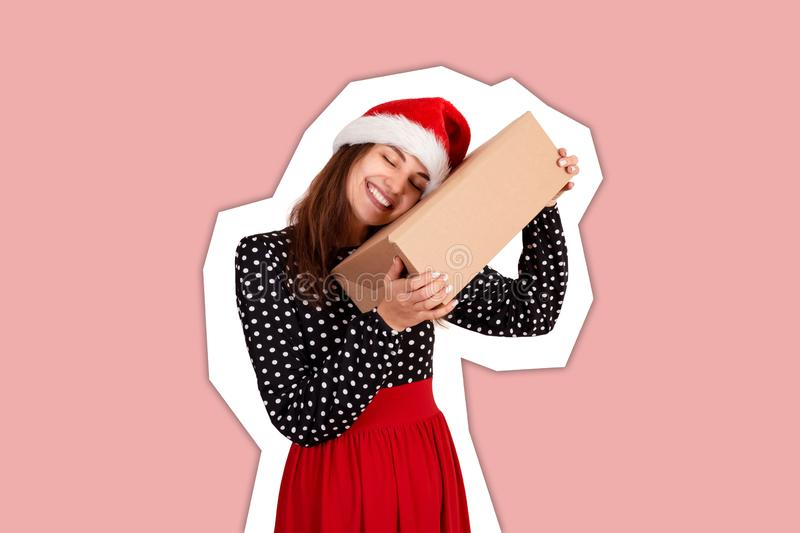 Happy brunette girl in christmas hat hugs the gift box. Magazine collage style with trendy color background. holidays concept.  royalty free stock photo