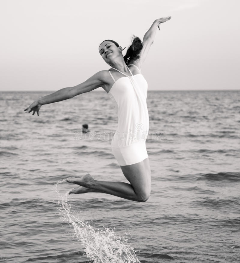 Happy brunette girl jumping over the sea. Stylized as retro photo royalty free stock images