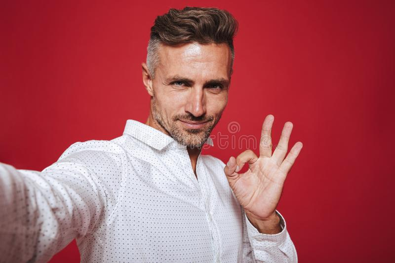 Happy brunette man 30s with stubble in white shirt taking selfie. Photo and showing ok sign isolated over red background stock images