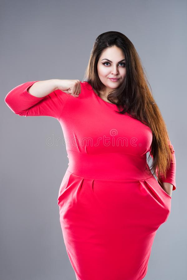 Happy brunette plus size model in red dress, fat woman with long hair on gray background, body positive concept royalty free stock photo