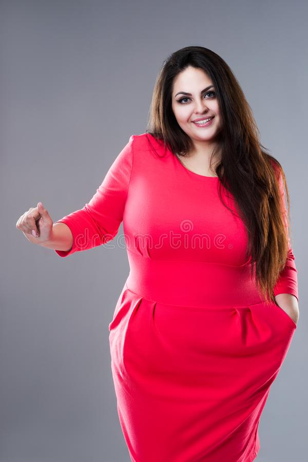 Happy brunette plus size model in red dress, fat woman with long hair on gray background, body positive concept royalty free stock photos
