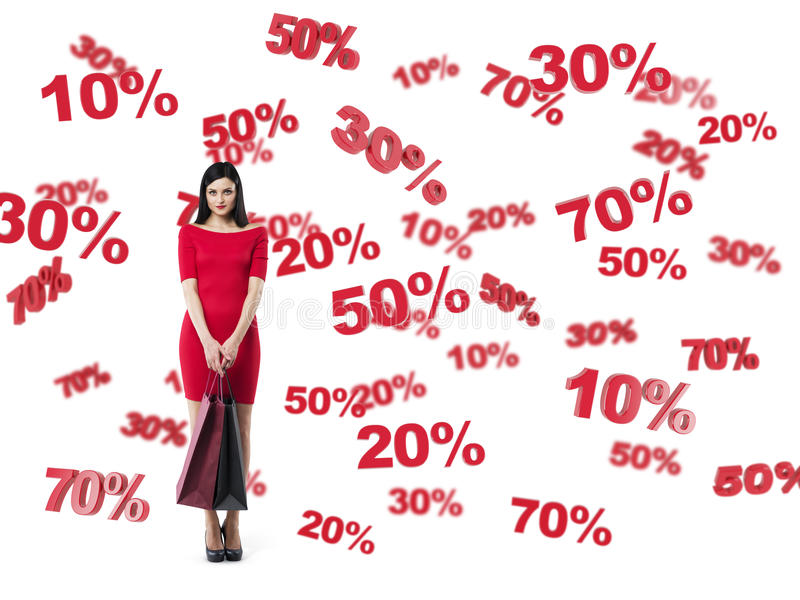 Happy brunette in a red dress with the shopping bags. Discount and sale symbols: 10% 20% 30% 50% 70%. Isolated royalty free stock photo