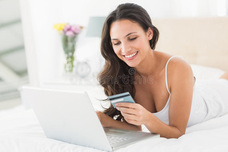 Happy brunette shopping online with laptop. At home in bedroom royalty free stock image