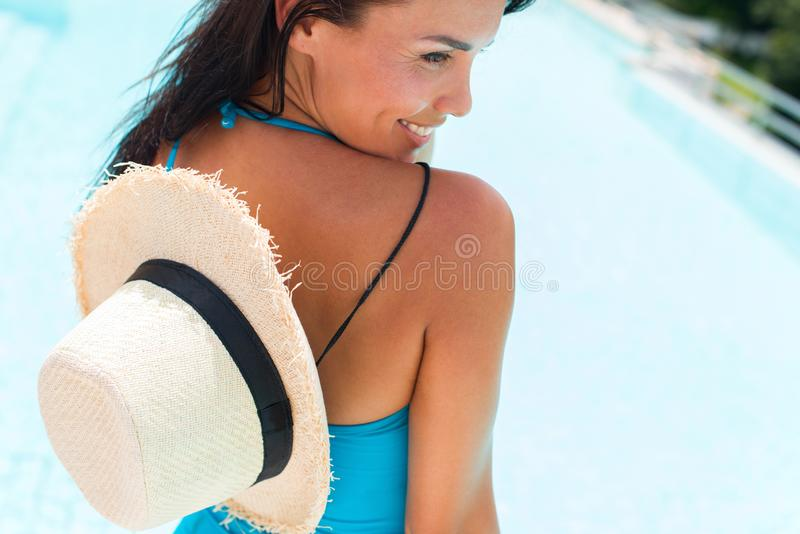 Happy brunette suntanned woman in blue swimsuit. And staw hat relaxing in swimming pool spa. Vacation and rest in tropical Thailand. Summer time. Ppoolside royalty free stock image